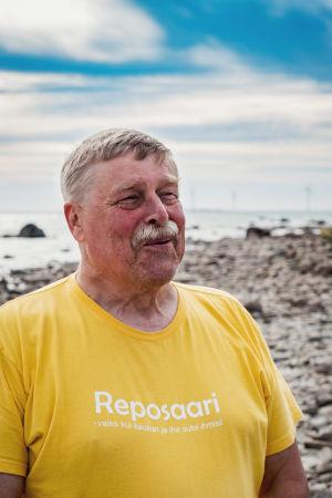 Mies keltaisessa t-paidassa rannalla, taustalla rantakiviä ja sinistä taivasta