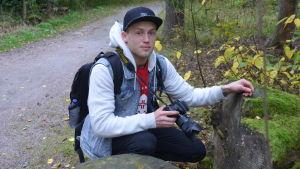 Person med kamera på huk vid sten och grusväg.
