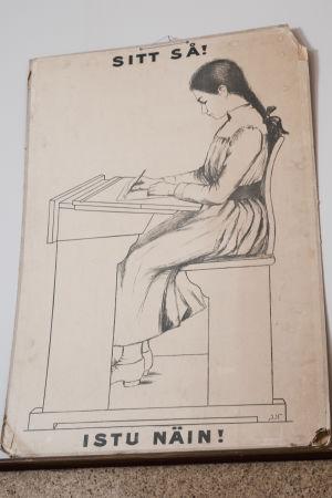 """Kyltti jossa kuva vanhanaikaisessa pulpetissa istuvasta tytöstä, vieressä kehotusteksti """"Istu näin!""""."""