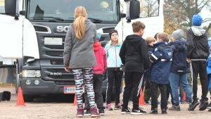 En grupp barn köar utanför en vit lastbil på en grusplan. En flicka med blont  hår och mössa står vänd mot kameran, resten har ryggen till.