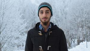 Rasim Al Sharkat ser in i kameran, i bakgrunden ett vackert vinterlandskap med frostiga träd.