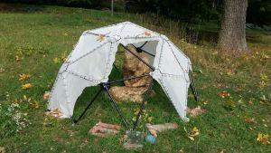 Ett kantigt tält med en liten figur är utställda på en gräsmatta under Konstrundan.