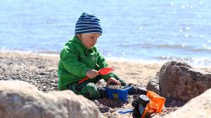 Ett barn leker i sanden.