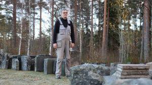 Församlingsmästare Olav Klemets står bland gravstenar som plockats bort från gravarna på Åsändans begravningsplats i Lappfjärd