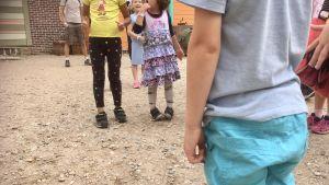 Barn står och väntar på att leken ska börja.
