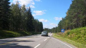 En bil susar fram på landsvägen.