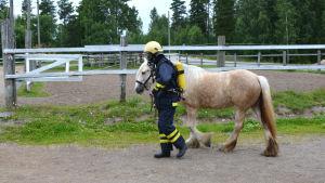 Man i brandutrustning leder beige häst