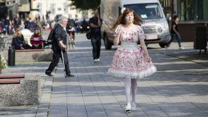 En kvinna klädd i så kallade Lolitakläder - en fluffig vit och rosa klänning med spetsar på. Hon har vita högklackade skor och blommor i håret. Hon går på en trottoar i centrum av Vasa. I bakgrunden tittar en äldre kvinna på henne.