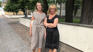 Irina Muuri och Anne Kiviniitty står bredvid varandra utomhus.