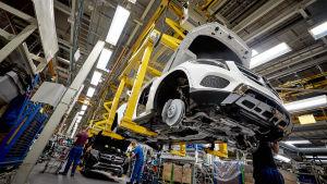 bilfabrik med en bil som är upphöjd i fabriken utan hjul.