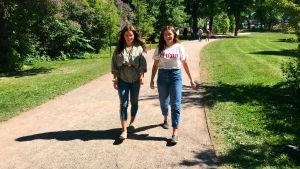 Två unga flickor går i solskenet i en park