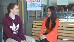 Gymnasieeleverna Tim Holmberg och Waranya Wessberg sitter i Karis-Billnäs gymnasiums aula och pratar med varandra.