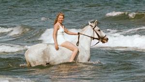 Nainen valkean ratsun selässä meren aalloissa. Kuva elokuvasta Muuttolintu (Opfergang), 1944.
