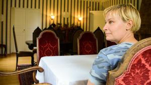 En kvinna sitter vid ett bord i en sal. Stolarna är i trä med sammetsbeklädda ryggstöd.