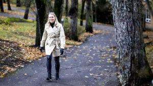 Susanne går i Vårdbergsparken, på marken ser man höstlöv.