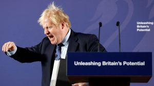 Boris Johnson står vid ett podium och håller tal. Han tittar neråt, viftar med handen och skriker.