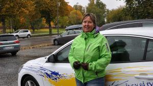 Ulla står vid trafikskolans vita bild som har reklamtejpning på utsidan.