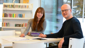 Linda Loimijoki och Janne Lahtia sitter vid ett bord i ett ljust bibliotek.