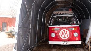 En rödvit glänsande Wolkswagen-bil står parkerad i ett grått biltält.