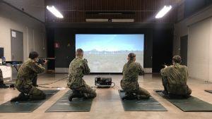Rekryter övar skjutning framför en stor bildskärm inne i en hall.