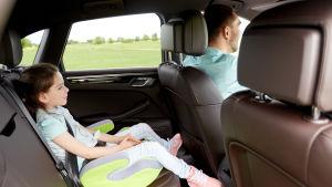 Ett barn i en bilstol på bakbänken i en bil med en manlig förare i framsätet som kör bredvid en grön äng.