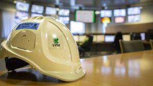 En skyddshjälm på ett bord i ett industriellt kontrollrum med många skärmar i bakgrunden.
