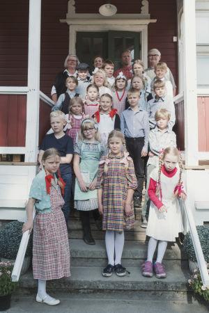 Koululuokallinen lapsia 1950-luvun vaatteisiin pukeutuneina poseeraavat koulun portailla.