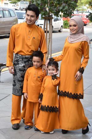 En muslimsk familj poserar för en kamera klädda i oranget med påklistrade leenden.