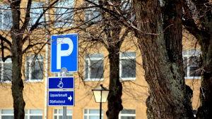 parkeringsskylt bland träd.