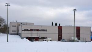 Skolbyggnad i snöigt landskap.