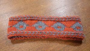 Ett mönsterstickat pannband med orange botten och gråa lador.
