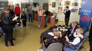 Ett rum fullt med människor som deltar i en valdebatt.