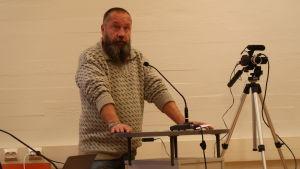 Janne Salonen står vid talarstolen.