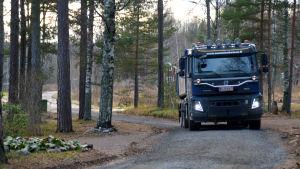 En lastbil kör på en grusväg.