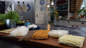 Erilaisia nuudeleita leikkuulaudalla keittiössä