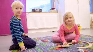 Dagisbarnen Eelis Mäki och Seela Raita leker på en bilmatta.