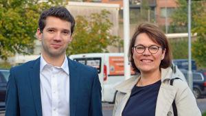 Ted Apter (Saml) och Martina Harms-Aalto poserar framför flaggstänger.