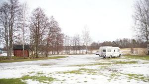 En öppen plats, kantad av några träd och som gränsar till havet. Där står två bilar parkerade.