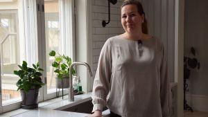 Åsa Björkman vid diskbänken i sitt ljusa kök.