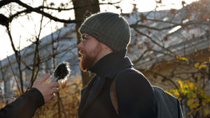 En man står med sidan mot kameran. En hand från vänster håller en bandspelare i höjd med mannens mun.