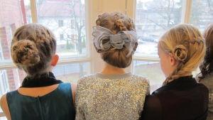 tre flickor står med ryggen till, de har flätade festfrisyrer.
