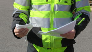 En man i svarta och neongula arbetskläder håller ett munskydd i ena handen och en bunt med papper i andra handen. Man ser inte ansiktet på mannen.