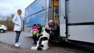 Kunder och hund utanför biblioteksbussen.