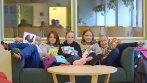 Fem barn i tioårsådern sitter i en soffa med böcker i händerna.