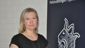 Ädre kriminalkonstapel Sara Malm står vid en banderoll med polisens lejonemblem.