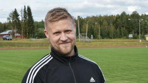 Mikael Kock iklädd sportdräkt tittar in i kameran. Idrottsplan i bakgrunden.