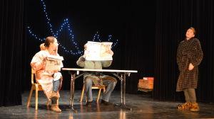 Tre personer på scen. En läser tidning.