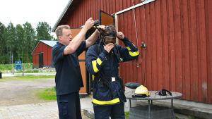 Man hjälper man i brandmansutrustning att ta på gasmask.