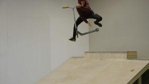 Kimi Futtari flyger i luften med sin sparkcykel.