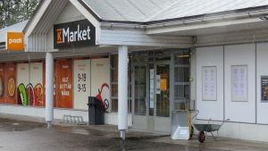 En K-market utiifrån. Butiken finns i Ingå. Det är regnväder. Utanför finns bland natta en skottkärra (som är till salu).